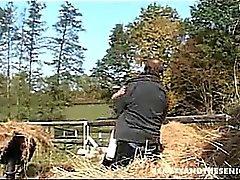 Ein Kerl verschiebt sich Heumaschinen und ein junges Mädchen ihn aufpaßt .