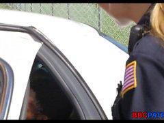 Blonde weibliche Polizei-Angebot saugt einen schwarzen Schwanz auf der Straße