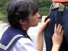 A menina japonesa sopra 2 homens na rua