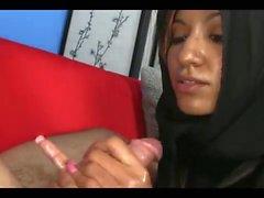 Muslim in Hijab saugt einen großen weißen Hahn BWC