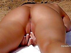 Heiße Blondine im schwarzen Bikini zeigt ihre riesigen Busen die auf Strand