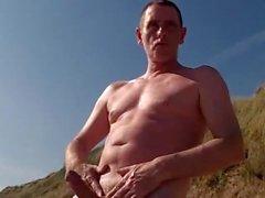 djärv exhibitionist balle av på stranden