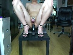 Sissy in chastity cage cums hands free while riding big black dildo