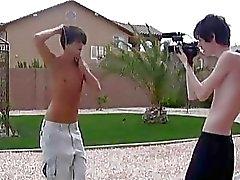 Playful homosexuella pojkar djurgarnif i framför kameran utomhus