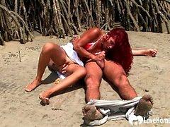 Rothaarigeküken, das Hahn saugt und auf Strand reitet