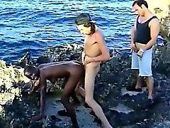 Schwarze Küken saugt weißen Hähne und wird am Strand gefickt
