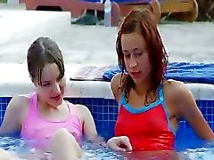 Lezzies molhadas beijando pela piscina