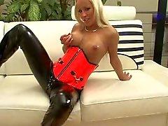 Blond Deutsch im schwarzen und roten Latex