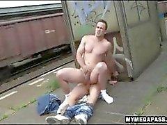 Två kåta killar knullar utomhus på en tågstation