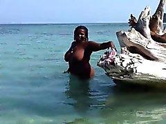 Fat black babe wades nus dans les shallows et joue avec h