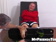 Kenny laughs hard while his feet is tickled on strap chair