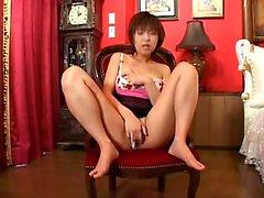 Abafado menina japonesa senta-se em uma cadeira e dedos-se a