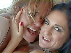 Kinky lesbians in sexy gear fuck on the couch with a toy